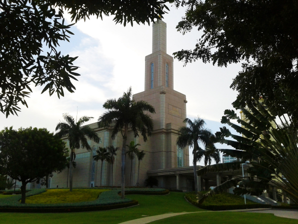 A side view of the Santo Domingo Dominican Republic Temple, with a partial view of the entrance and the grounds covered in trees.
