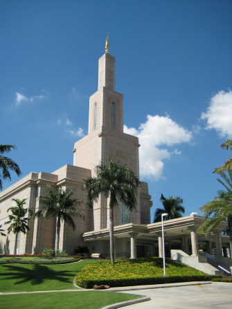 The entrance to the Santo Domingo Dominican Republic Temple, with a view of the angel Moroni on the spire and the trees on the grounds around the temple.