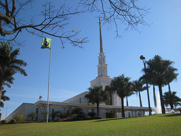 The entire São Paulo Brazil Temple, including a view of the grounds, with palm trees and a partial view of the fountain in front of the temple.
