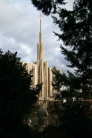 The Seattle Washington Temple, with a partial view of the front, framed by trees on the grounds of the temple.