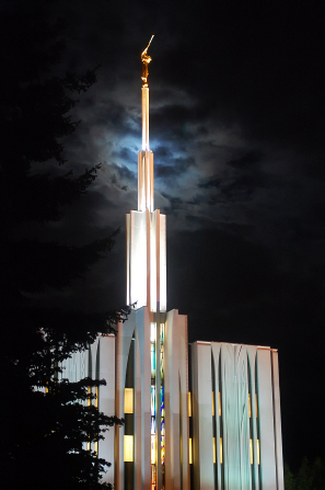 A view of the Seattle Washington Temple spire all lit up at night, with the windows on the temple lit up from inside.