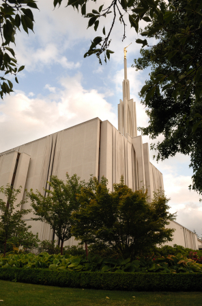 A partial view of the side of the Seattle Washington Temple, with a view of the spire, framed by green trees.