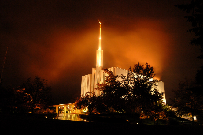 The Seattle Washington Temple during a storm, with the temple lit up at night.