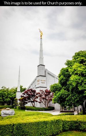 A front view of grass, bushes, and trees surrounding the Seoul Korea Temple on a cloudy day.