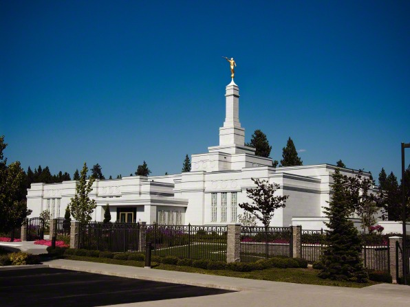 The front of the Spokane Washington Temple, including a view of the entrance, the fence, and trees on the grounds.