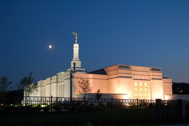The entire Spokane Washington Temple lit up at night, with a view of the moon in the background.