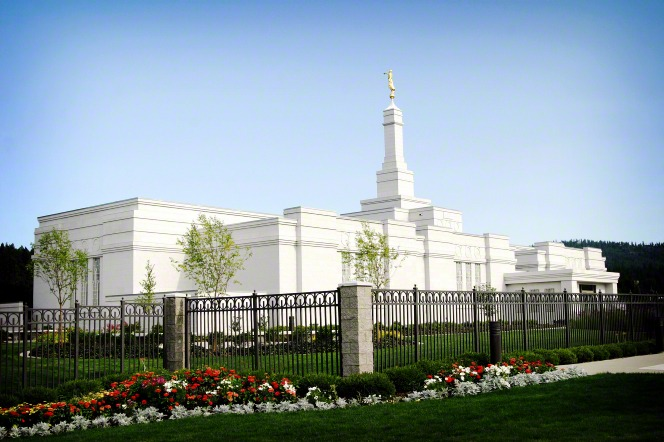 The entire Spokane Washington Temple during the daytime, with grounds surrounded by a fence, lined with flowers and trees.