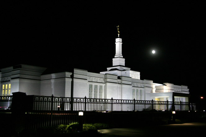 The side of the Spokane Washington Temple, with a view of the fence around the grounds, all lit up at night.