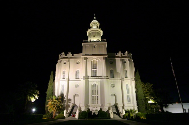 A view up the front of the St. George Utah Temple, including the two staircases and two doors, all lit up at night.