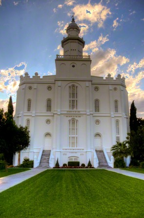 The front of the St. George Utah Temple, with a view of the grass leading up to the front and staircases leading up to the doors.