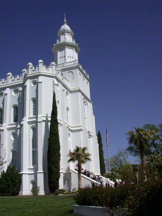 The front of the St. George Utah Temple, with a view of the spire, entrance, and grounds.