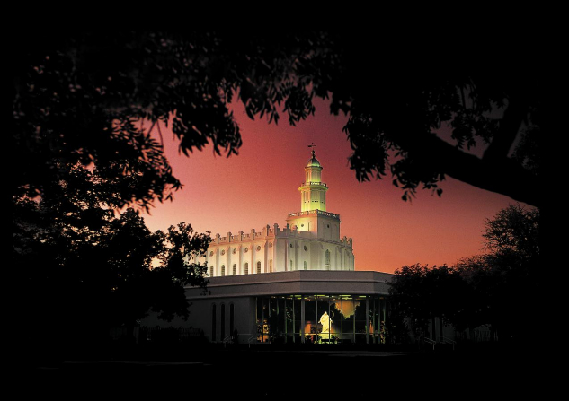 The St. George Utah Temple lit up in the evening, with a view of the visitors' center nearby and the Christus inside, all surrounded by trees.
