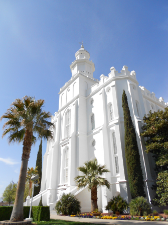 The front of the St. George Utah Temple, with a view of the spire, entrance, and grounds with trees.