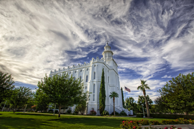 The entire St. George Utah Temple, with a view of clouds in the sky above and with the surrounding grounds covered in trees, flowers, grass, and bushes.