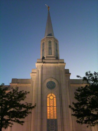 A front view of the St. Louis Missouri Temple in the evening, with trees on either side and the windows lit up from the inside.
