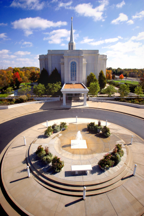 The fountain on the grounds of the St. Louis Missouri Temple, with the temple in the background and a view of the grounds surrounding the temple.