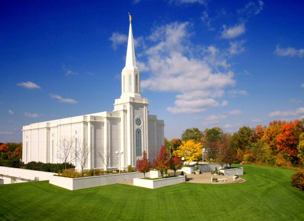 The entire St. Louis Missouri Temple in the fall, with a view of the grounds covered in grass and trees changing colors.