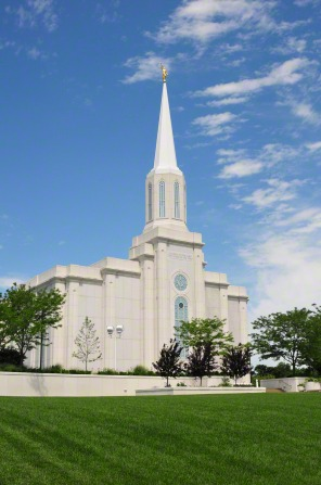 A view of the front of the St. Louis Missouri Temple, with a partial view of the grounds with trees.
