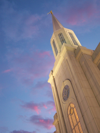 A view up the spire of the St. Louis Missouri Temple in the evening, with a partial view of the windows lit up from inside.
