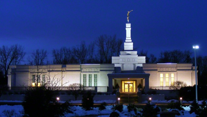 The entire St. Paul Minnesota Temple all lit up at night during the winter, with a view to the entrance. Snow is on the ground around the temple.