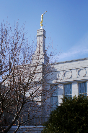 A partial view of the St. Paul Minnesota Temple through trees on the grounds, including a view of the spire.