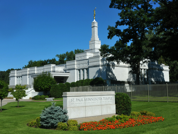 The entire St. Paul Minnesota Temple, with trees, bushes, and red flowers around the temple name sign.