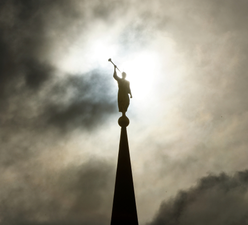 An image of the Angel Moroni on the Star Valley Wyoming Temple, silhouetted against a darkly clouded sky.