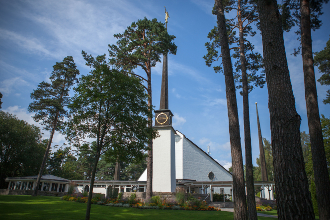 The entire Stockholm Sweden Temple, with trees on the grounds in front of the temple. The view includes the entrance, spire, and grounds.