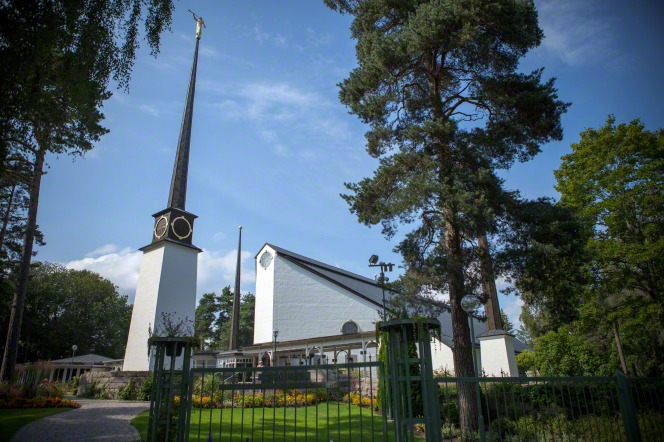 The entrance to the grounds of the Stockholm Sweden Temple through the gate, with the entire temple in view surrounded by trees.