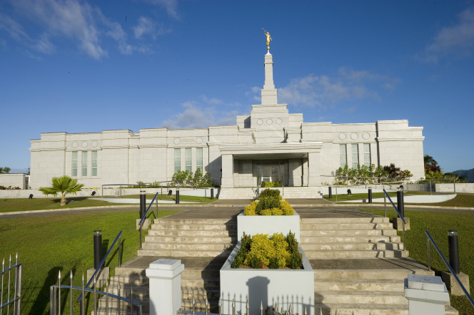 The front entrance to the Suva Fiji Temple during the daytime, with the stairs on the grounds leading to the entrance.