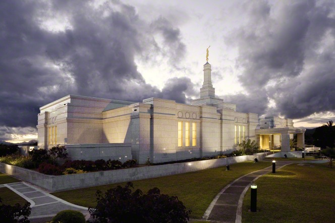A view of the side of the Suva Fiji Temple, including the path through the grounds leading to the entrance, with the temple lit up in late evening.