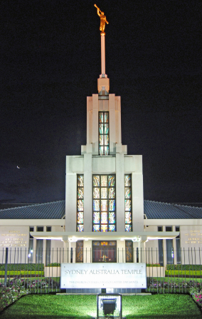 The front of the Sydney Australia Temple, with the spire, stained-glass windows, doors, and temple name sign.