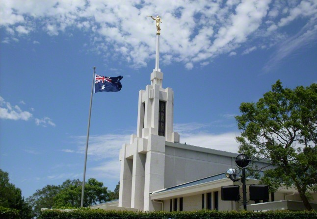 A side view of the front of the Sydney Australia Temple, with the Australian flag flying on the grounds.