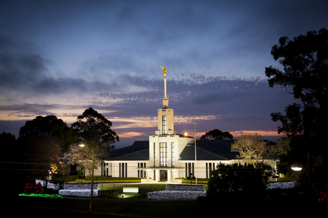 The entire Sydney Australia Temple, including the entrance, the spire, and the angel Moroni on top, with a fence surrounding the grounds, all lit up at night.