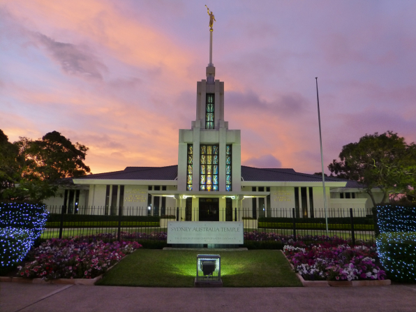 The front entrance to the Sydney Australia Temple, including a partial view of the grounds and fence and a view of the temple name sign.