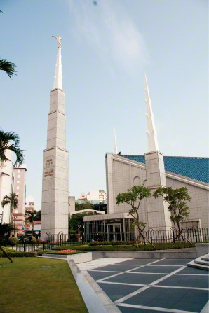 A daytime image of the Taipei Taiwan Temple, with a view of the entrance and two spires and a partial view of the grounds.