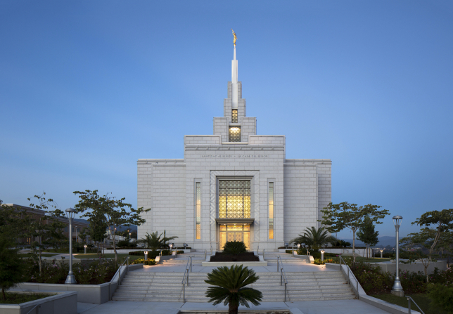 The entrance to the Tegucigalpa Honduras Temple in the evening, with stairs leading to the doors, lit up at night.