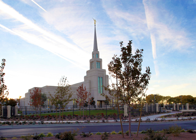 The Gila Valley Arizona Temple in the evening, with the fence surrounding the grounds, trees, and bushes.