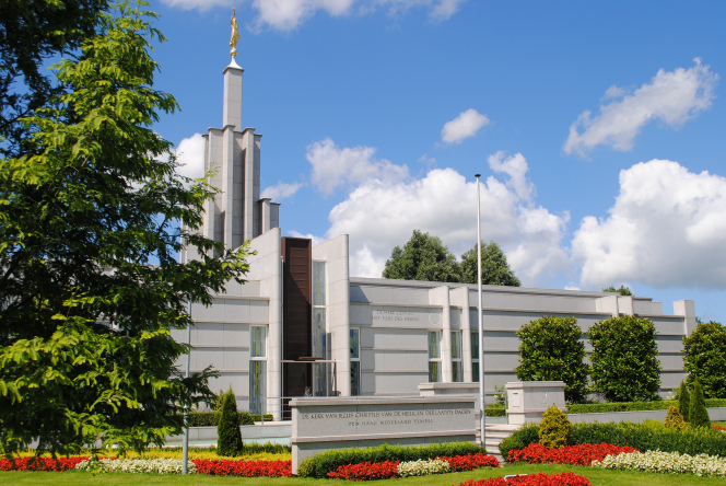 The front of The Hague Netherlands Temple, with the temple name sign and flowers on the grounds.