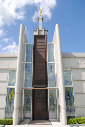 The front entrance of The Hague Netherlands Temple, with a view of windows, doors, and the angel Moroni on the spire.