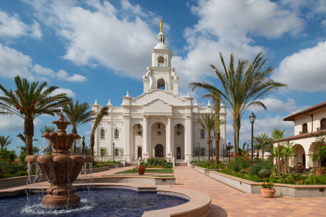 The Tijuana Mexico Temple during the day, with a fountain and palm trees in the foreground.