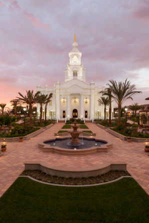 A fountain, sidewalks, and vegetation outside the Tijuana Mexico Temple, with a sunset in the background.
