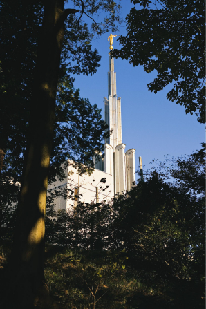 A view of the spire of the Tokyo Japan Temple through the trees on the grounds.