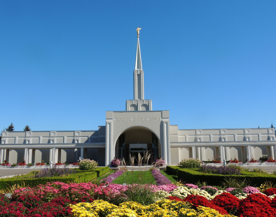The front entrance to the Toronto Ontario Temple, with the grounds, including flowers and bushes.
