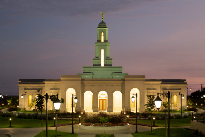 A front view of the Trujillo Peru Temple at dusk, with a purple sky overhead and a row of street lamps leading to the entrance.