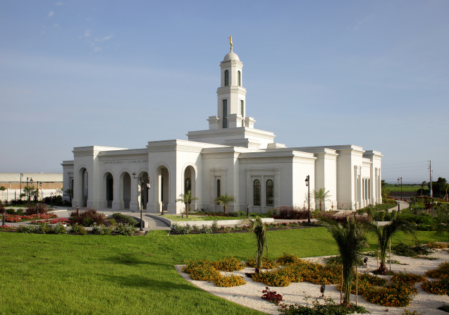 A side view of the Trujillo Peru Temple on a sunny day, with palm trees and other local plants growing on the grounds.
