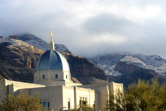 A photograph of the Tucson Arizona Temple with snow-dusted mountains in the distance.