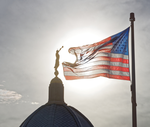 A photograph of the Tucson Arizona Temple dome and Angel Moroni statue with an American flag backlit by the sun.