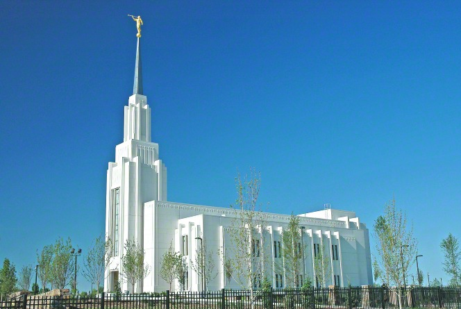 The side of the Twin Falls Idaho Temple during the day, with the fence and trees.