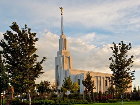 A side view of the Twin Falls Idaho Temple in the evening, with the grounds, trees, and fence.